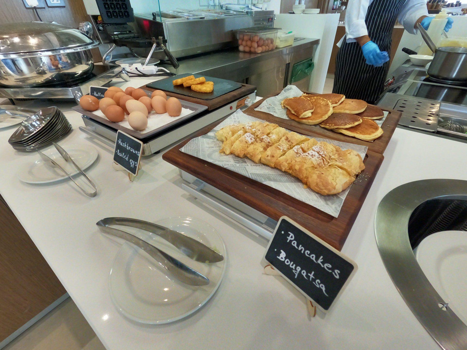 Pancakes, bougatsa (greek pastry), hash browns and boiled eggs